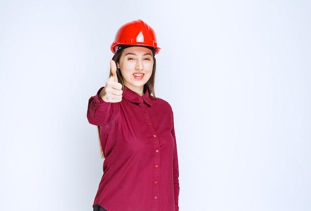 Pomyślny architekt żeński w czerwonym hełmie twardym dając aprobaty.