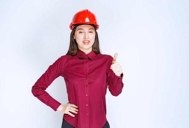 Pomyślny architekt żeński w czerwonym kasku twardym stojąc i dając aprobaty.