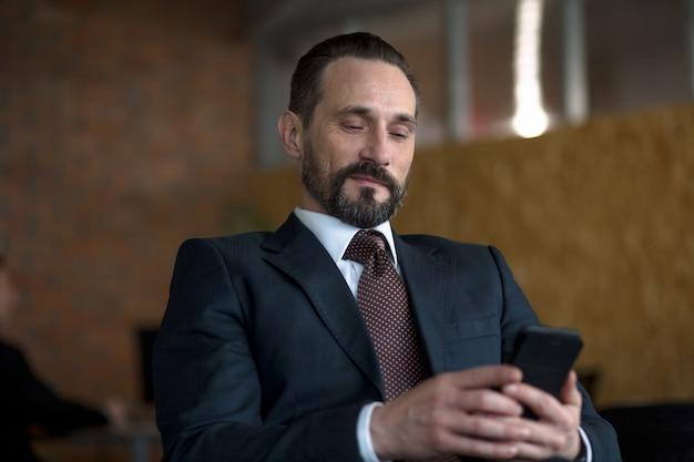 Pomyślny biznesmen czyta wiadomość tekstową na telefonie komórkowym podczas gdy siedzący w jego biurze.