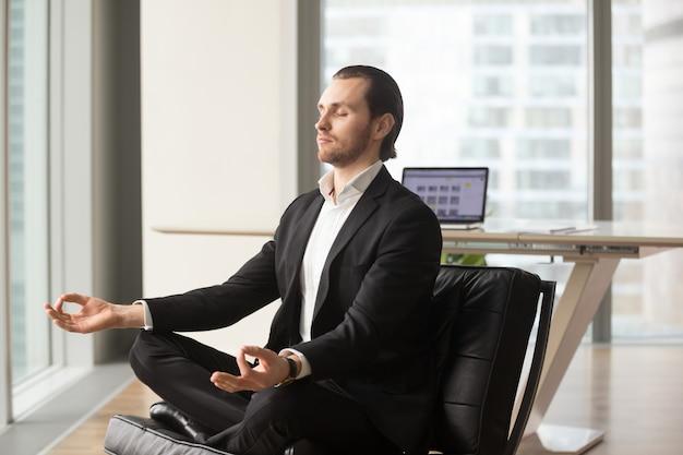 Pomyślny biznesmen medytuje przy miejscem pracy