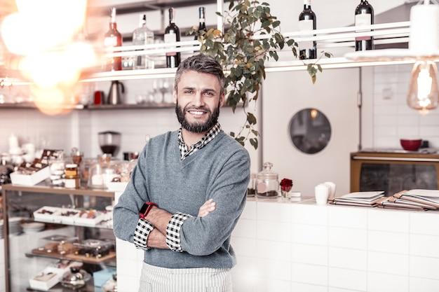 Pomyślny biznesmen. przystojny, zachwycony mężczyzna będący w świetnym nastroju, prowadzący kawiarnię, która odniosła sukces