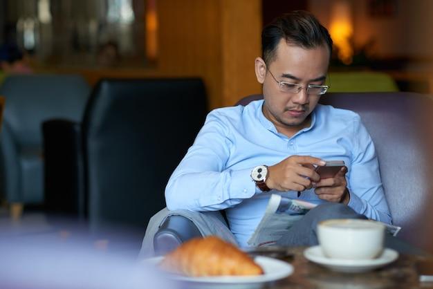 Pomyślny biznesmen sprawdza smartphone nad śniadaniem w kawiarni