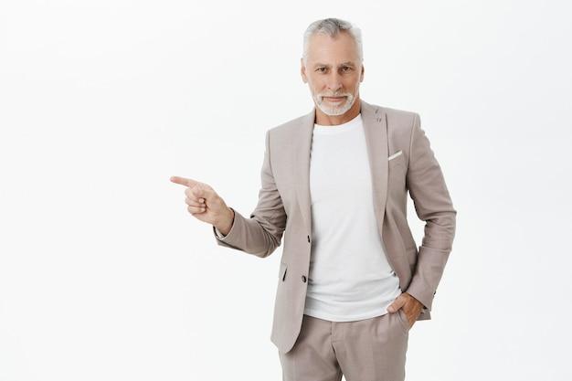 Pomyślny biznesmen uśmiechający się wskazujący palec w lewo