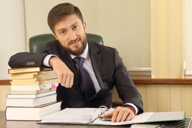 Pomyślny biznesmen w biurze z książkami i dokumentami
