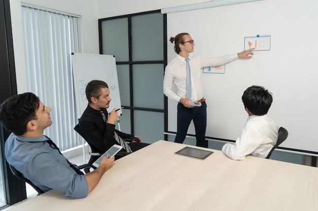 Pomyślny biznesmen wskazuje przy dane podczas pięcioliniowego spotkania.