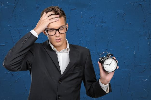 Pomyślny biznesmen wskazuje przy zegarem w formalnej odzieży
