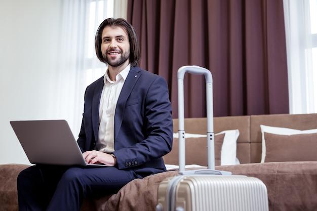 Pomyślny biznesmen. zadowolony pozytywny mężczyzna pracujący na laptopie w pokoju hotelowym