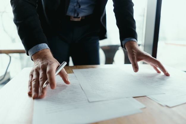Pomyślny biznesowego mężczyzna podpisywania dokumenty w nowożytnym biurze