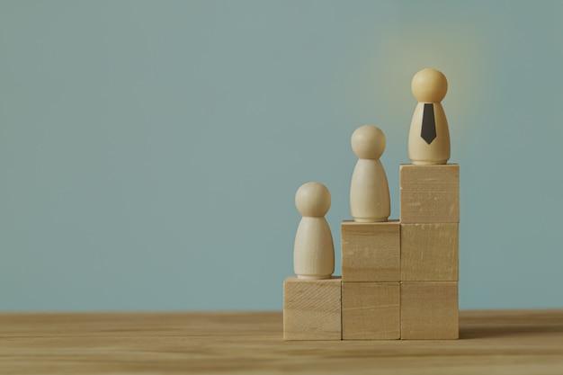 Pomyślny biznesowy lidera zespołu pojęcie: biznesmen pozycja w najwyższym punkcie na drewnianym bloku.