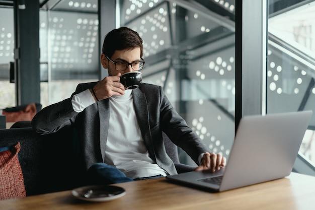 Pomyślny biznesowy mężczyzna pracuje na laptopie podczas gdy pijący kawę