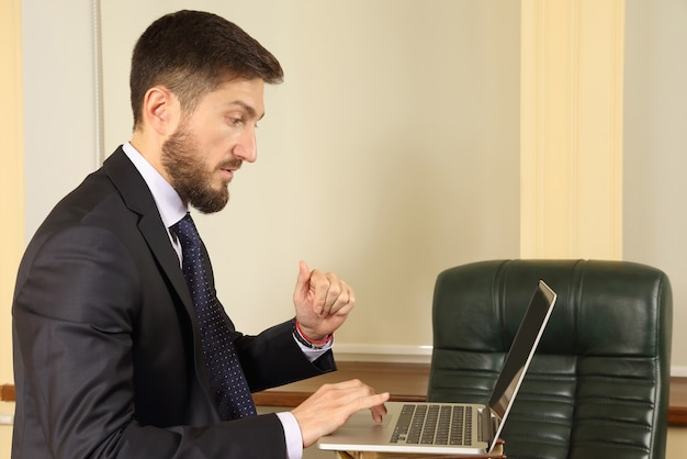 Pomyślny biznesowy mężczyzna w biurze pracy z laptopem