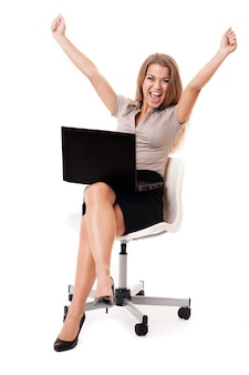 Pomyślny bizneswoman z laptopem na kolanach