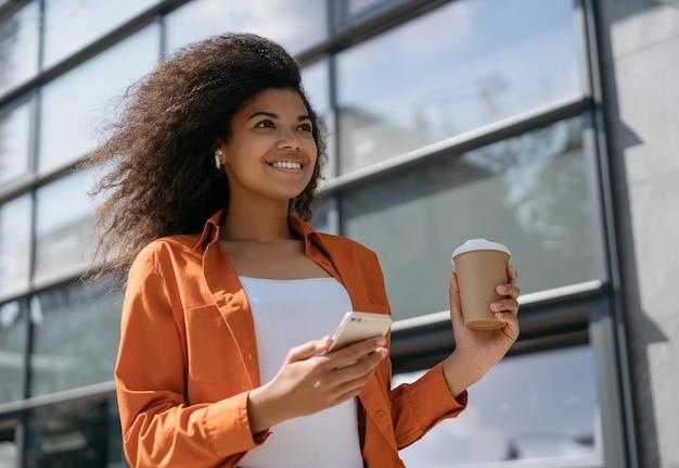 Pomyślny bizneswomanu mienia telefon komórkowy, filiżanka kawy, słuchanie muzyki na ulicie