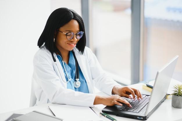 Pomyślny czarny lekarz kobieta uśmiecha się w biurze