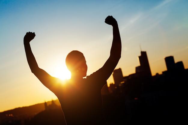 Pomyślny człowiek z podniesionymi rękami o zachodzie słońca