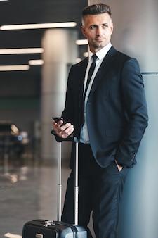 Pomyślny dojrzały biznesmen trzyma telefon komórkowy