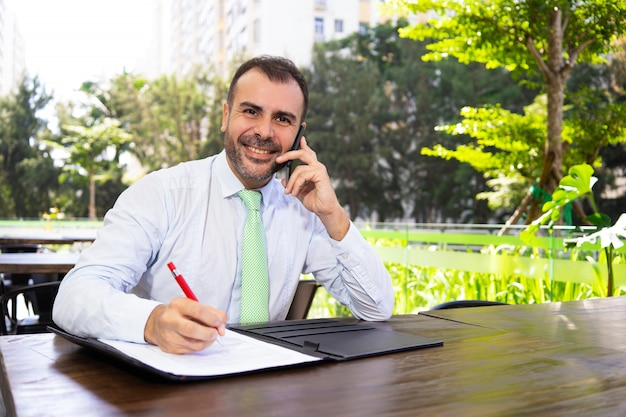 Pomyślny dojrzały kierownik opowiada na telefonie i czytelniczym dokumencie