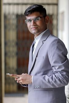 Pomyślny indiański biznesmen używa smartphone