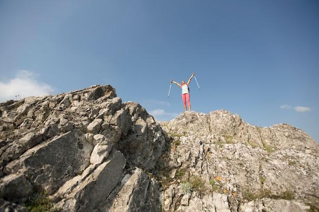 Pomyślny kobieta wycieczkowicza otwarte ręki przy halnym szczytem