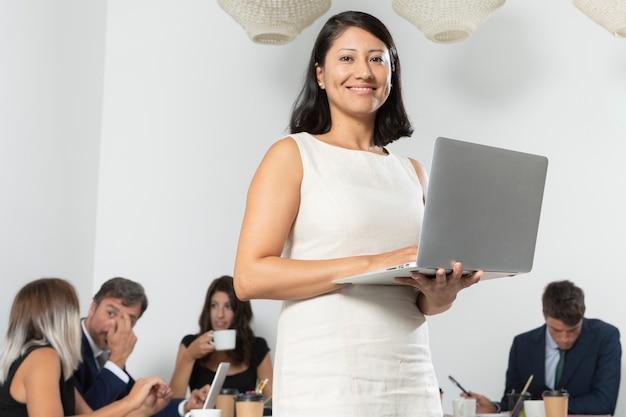 Pomyślny kobiety mienia laptopu środka strzał