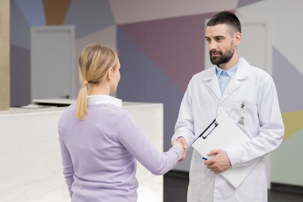 Pomyślny lekarz w białym fartuchu patrząc na młodą blond pacjentkę, ściskając jej rękę po konsultacji lub badaniu