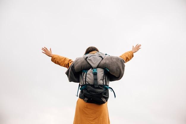 Pomyślny młodej kobiety backpacker otwarte ręki przeciw niebu