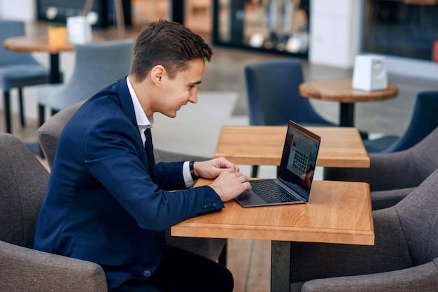 Pomyślny młody biznesmen pracuje na laptopie w sklep z kawą
