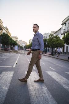 Pomyślny młody biznesmen spaceru na ulicy w ciągu dnia
