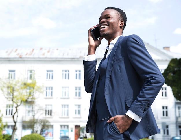 Pomyślny młody biznesmen z rękami w jego kieszeni opowiada na telefonie komórkowym