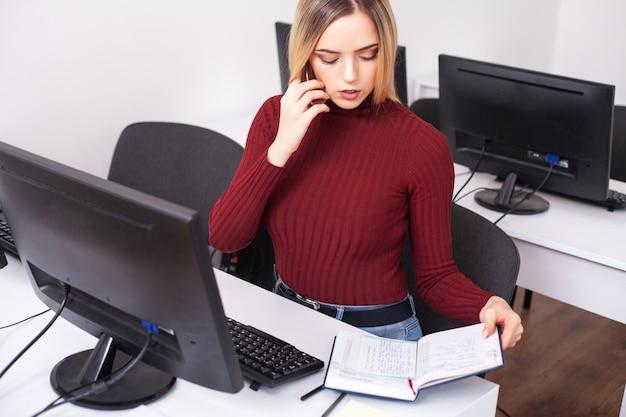 Pomyślny młody bizneswoman opowiada na telefonie komórkowym