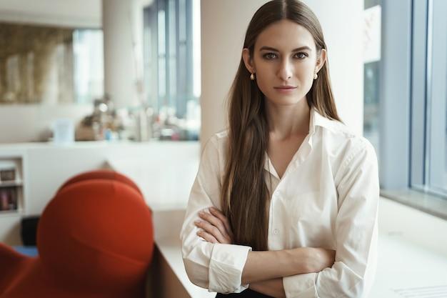 Pomyślny młody bizneswoman stoi w przestrzeni coworkingowej, patrząc pewnie.