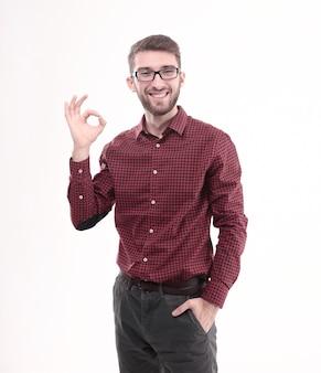 Pomyślny młody człowiek w okularach pokazujący znak ok. na białym tle