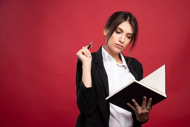 Pomyślny pracownik czyta książkę pamięci na czerwonym tle.