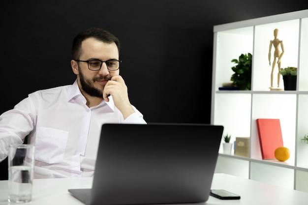 Pomyślny przystojny biznesmen robi rozmowie wideo w domowym biurze, zdalna praca
