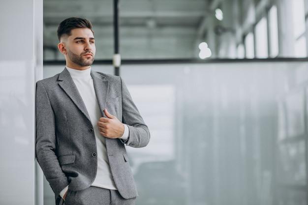 Pomyślny przystojny biznesowy mężczyzna w biurze