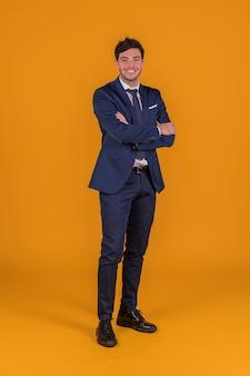 Pomyślny przystojny uśmiechnięty młody człowiek z jego ręką krzyżował pozycję przeciw pomarańczowemu tłu