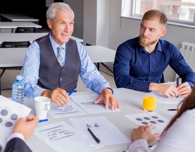 Pomyślny starszy biznesmen z jego kolegą w spotkaniu