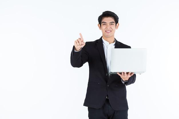 Pomyślny szczęśliwy azjatyckiego młodego biznesmena udany biznes trzymać komputer przenośny z wskazującymi gestami dłoni palcem dotykowym panelu obrazowania na białym tle
