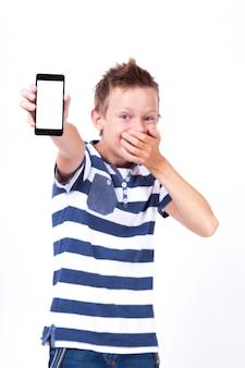 Pomyślny uczeń z telefonem w jego ręce na bielu