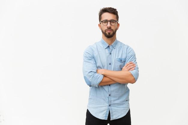 Pomyślny ufny męski przedsiębiorca pozuje z rękami składać