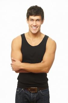 Pomyślny umięśniony młodego człowieka ono uśmiecha się