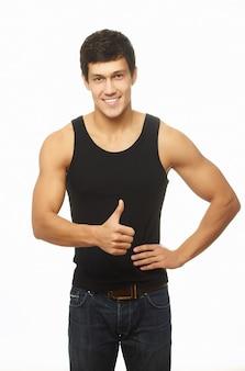 Pomyślny umięśniony młody człowiek pokazuje kciuk up i ono uśmiecha się