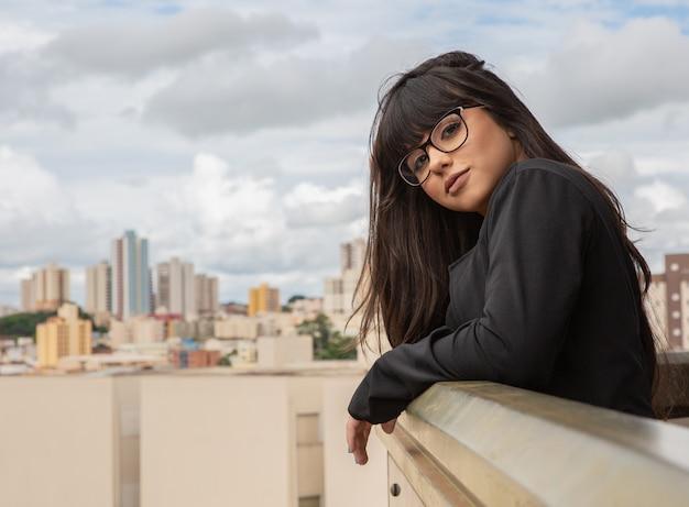 Pomyślny uśmiech bizneswoman na górze budynku.