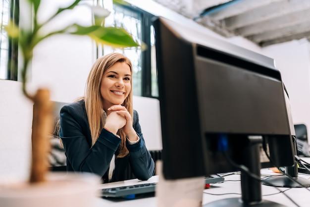 Pomyślny uśmiechnięty bizneswomanu obsiadanie przy biurem przed komputerem.