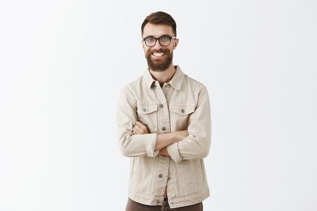 Pomyślny, uśmiechnięty brodaty mężczyzna w okularach, pozowanie na białej ścianie