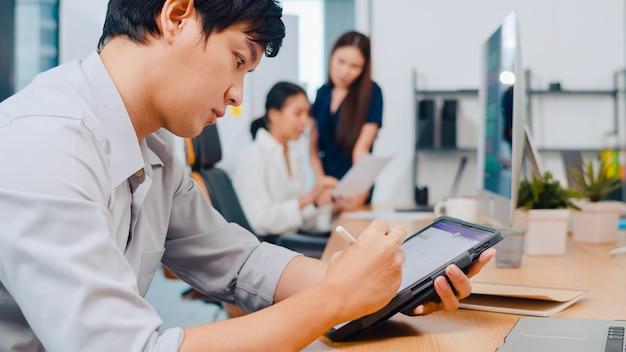 Pomyślny wykonawczy asia młodego biznesmena mądrze przypadkowy odzież rysuje, pisze i używa pióro z cyfrowym pastylki komputerowym główkowaniem inspiraci rewizi pomysłów pracuje proces w nowożytnym biurze.