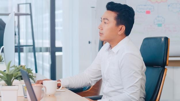 Pomyślny wykonawczy azjatyckiego młodego biznesmena mądrze przypadkowa odzież używać komputer stacjonarny główkowanie inspiraci rewizi pomysłów rozwiązania problemowi pomysły gubili podczas pracy w nowożytnym biurowym miejscu pracy.