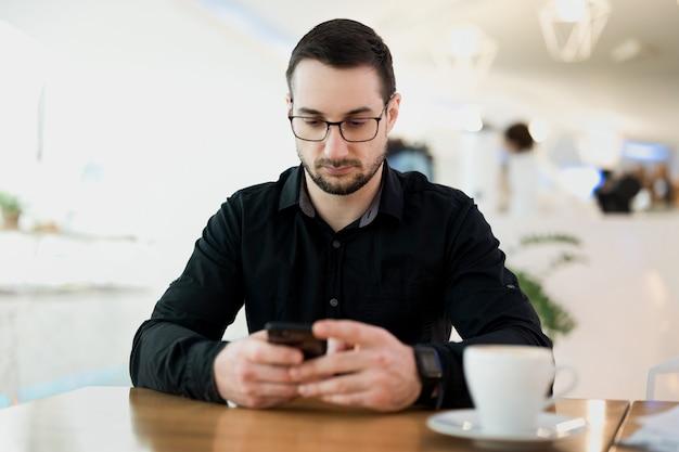 Pomyślny zdalny pracownik płci męskiej. młody freelancer człowiek zadowolony z rozmowy telefonicznej. sklep z kawą na tle. męski programista freelancer pracujący w kawiarni. chętnie rozmawia z klientem.