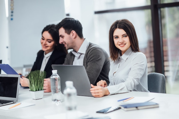 Pomyślny żeński używa laptop na jej pracie w biurze.