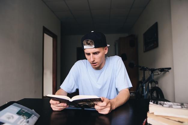 Pomyślony młody człowiek czyta w pokoju ciekawą książkę w domu. nauczanie w domu.